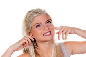 Frau leidet unter Lärmbelästigung, hält sich die Ohren zu